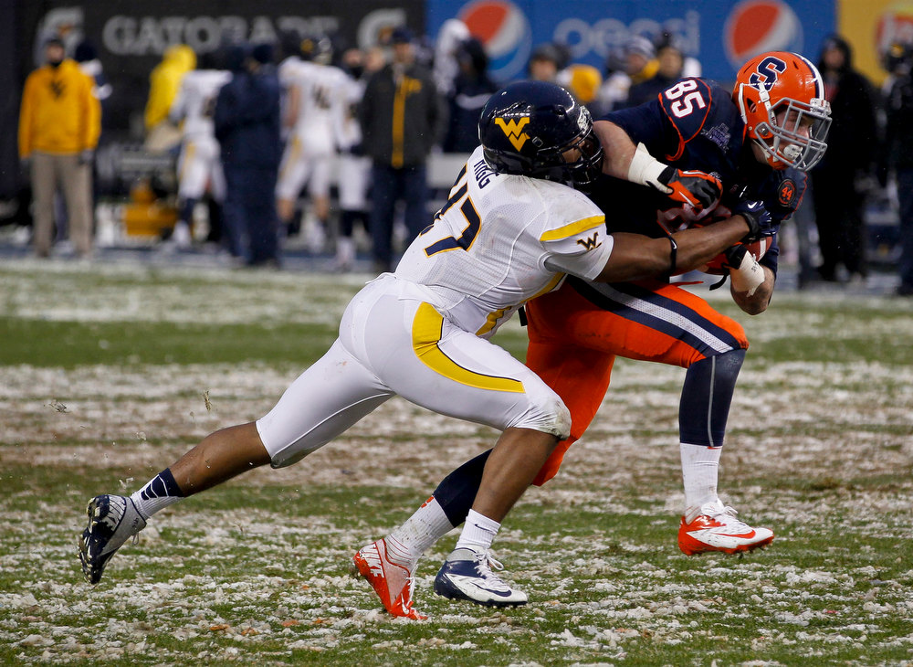 Description of . Doug Rigg #47 of the West Virginia Mountaineers tries to take down Beckett Wales #85 of the Syracuse Orange in the New Era Pinstripe Bowl at Yankee Stadium on December 29, 2012 in the Bronx borough of New York City.  (Photo by Jeff Zelevansky/Getty Images)