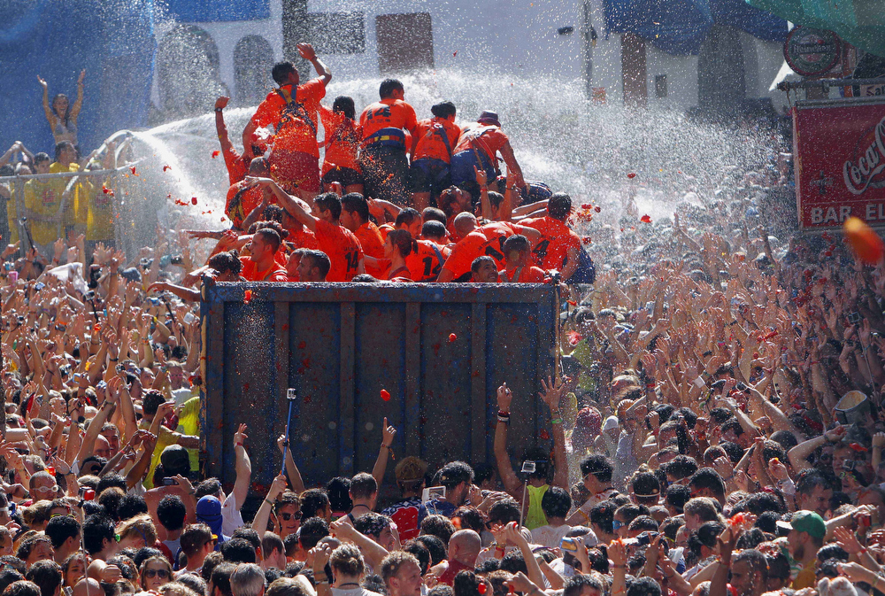 ". Crowds of people throw tomatoes at each other, during the annual ""tomatina\"" tomato fight fiesta, in the village of Bunol, 50 kilometers outside Valencia, Spain, Wednesday, Aug. 27, 2014. The streets of an eastern Spanish town are awash with red pulp as thousands of people pelt each other with tomatoes in the annual \""Tomatina\"" battle that has become a major tourist attraction. At the annual fiesta in Bunol on Wednesday, trucks dumped 125 tons of ripe tomatoes for some 22,000 participants, many from abroad to throw during the hour-long morning festivities.  (AP Photo/Alberto Saiz)"
