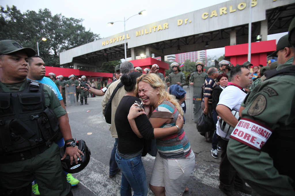 . Supporters of Venezuela\'s President Hugo Chavez embrace outside the military hospital after learning that Chavez has died through an announcement by Venezuela\'s vice president in Caracas, Venezuela, Tuesday, March 5, 2013. Venezuela\'s Vice President Nicolas Maduro announced that Chavez died on Tuesday at age 58 after a nearly two-year bout with cancer. During more than 14 years in office, Chavez routinely challenged the status quo at home and internationally. He polarized Venezuelans with his confrontational and domineering style, yet was also a masterful communicator and strategist who tapped into Venezuelan nationalism to win broad support, particularly among the poor. (AP Photo/Fernando Llano)