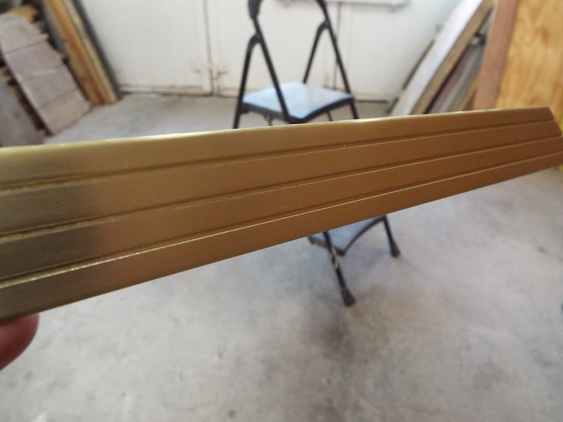 A piece of floor trim after being anodized gold.