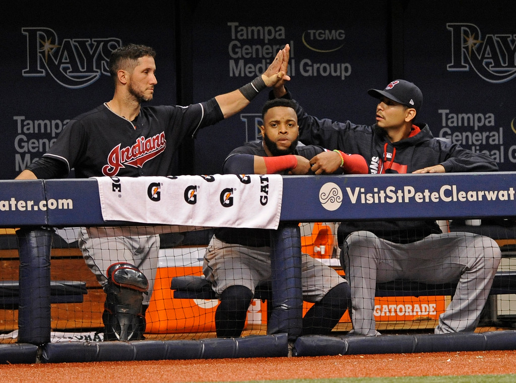 . Cleveland Indians catcher Yan Gomes, left, high-fives pitcher Carlos Carrasco, right, over Carlos Santana in the dugout during the ninth inning of a baseball game against the Tampa Bay Rays, Friday, Aug. 11, 2017, in St. Petersburg, Fla. (AP Photo/Steve Nesius)