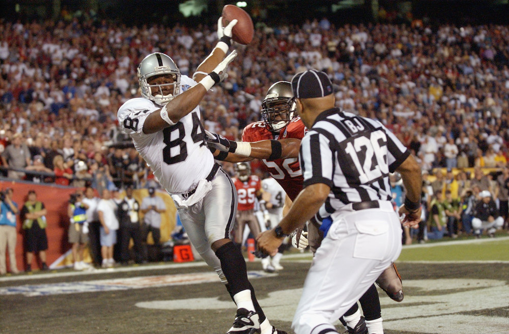 Description of . Jerry Porter #84 of the Oakland Raiders is pushed out of the end zone by Nate Webster #52 of the Tampa Bay Buccaneers on an unsuccessful two-point conversion attempt as Back Judge Don Carey #126 watches at 6:06 of the fourth quarter of Super Bowl XXXVII on January 26, 2003 at Qualcomm Stadium in San Diego, California. The Buccaneers defeated the Raiders 48-21. (Photo by Doug Pensinger/Getty Images)