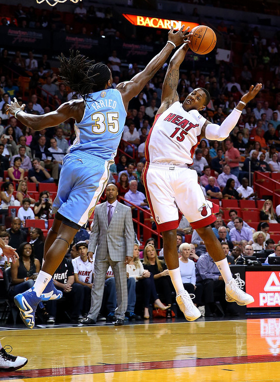 . MIAMI, FL - MARCH 14:  Kenneth Faried #35 of the Denver Nuggets is defended by Mario Chalmers #15 of the Miami Heat during a game  at American Airlines Arena on March 14, 2014 in Miami, Florida. (Photo by Mike Ehrmann/Getty Images)