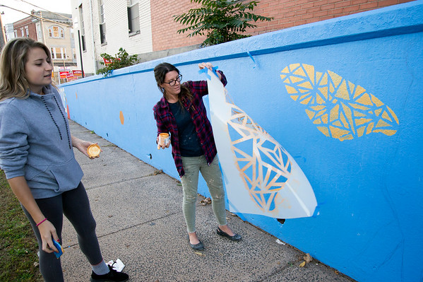 10/15/19 Wesley Bunnell | StaffrrCCSU art students spent part of Tuesday painting on East St near East Main St as part of a course called Art in Community taught by art professor Ted Efremoff. Danielle Pelkowski, L, from New Britain watches as Brooke Nightingale peels a stencil off of the wall.