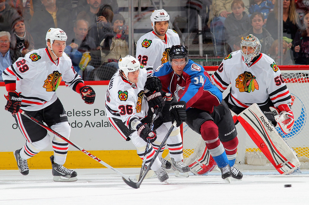 . DENVER, CO - MARCH 08:  Dave Bolland #36 of the Chicago Blackhawks clears the puck against David Jones #54 of the Colorado Avalanche at the Pepsi Center on March 8, 2013 in Denver, Colorado.  (Photo by Doug Pensinger/Getty Images)