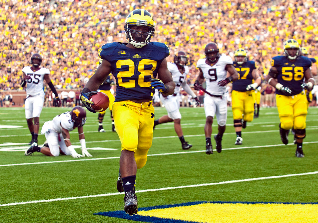 . Michigan running back Fitzgerald Toussaint  rushes for a 12-yard touchdown in the third quarter. (AP Photo/Tony Ding)
