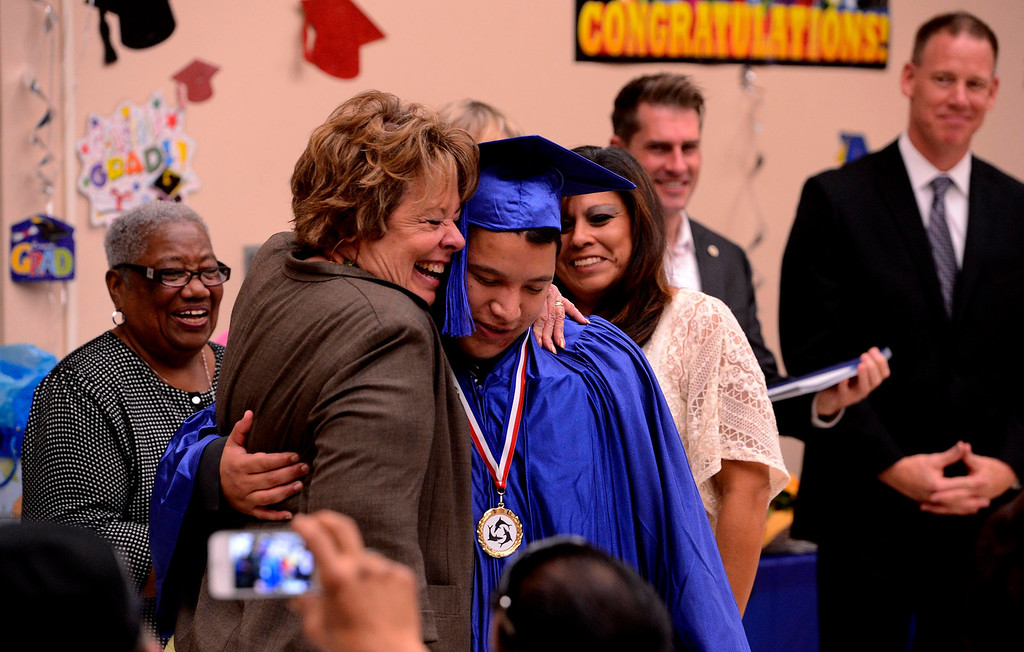 . Judy Penman hugs graduate Dominic Vasquez during Commencement Ceremonies at Carl And Dora Anderson School in San Bernardino May 21, 2013.  GABRIEL LUIS ACOSTA/STAFF PHOTOGRAPHER.