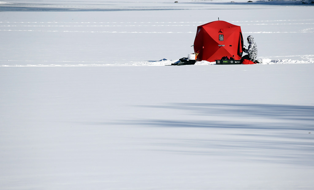 . An ice fisherman kneels by his shelter on Lake Cochichewick, Monday, Jan. 9, 2017, in North Andover, Mass. As the East Coast waits to thaw out from a weekend icy mess, another storm is bringing rain and the potential of the worst flooding in more than a decade to the West coast. (AP Photo/Elise Amendola)