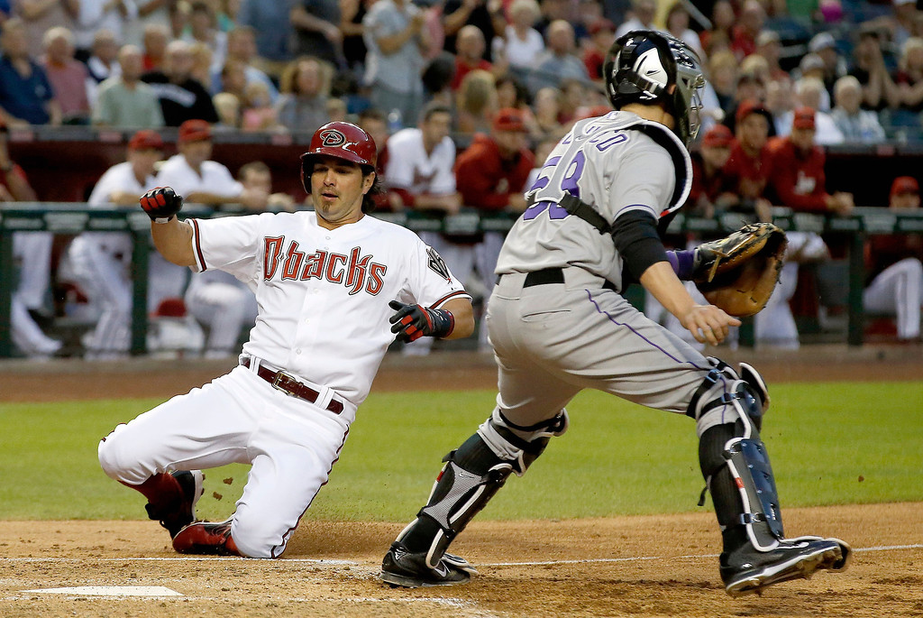 . Arizona Diamondbacks\' Eric Chavez, left, slides into home plate to score a run as Colorado Rockies\' Jordan Pacheco waits for a late throw during the second inning of a baseball game on Tuesday, April 29, 2014, in Phoenix. (AP Photo/Ross D. Franklin)