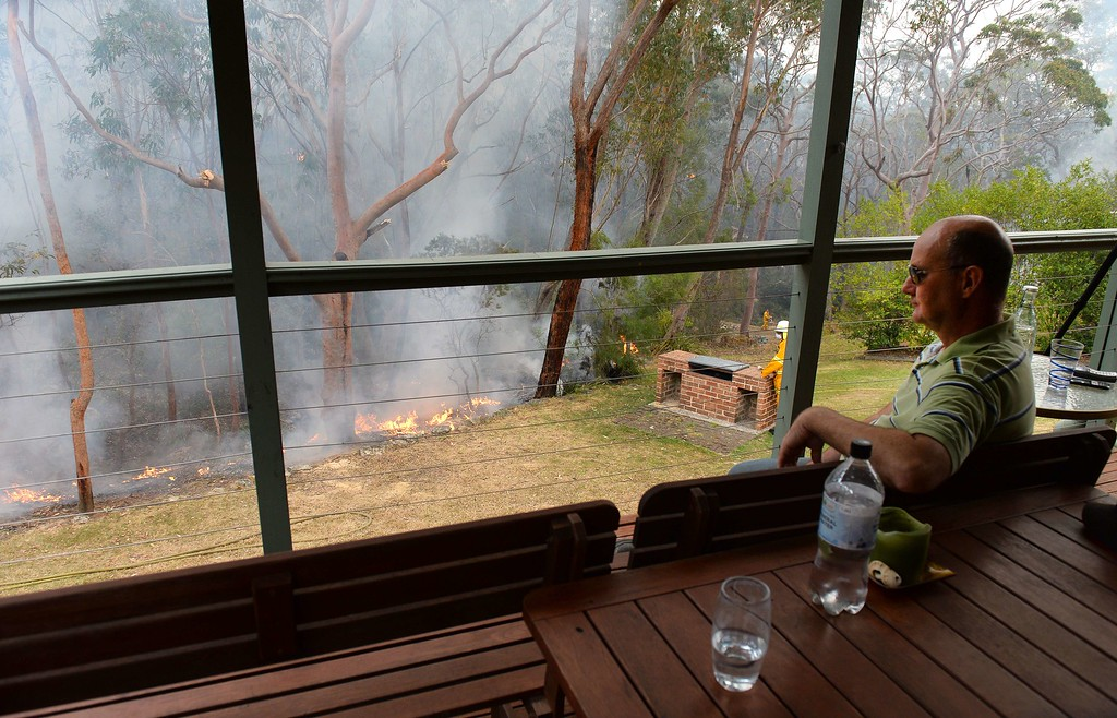 . Local resident Paul Chester watches the containment fires from the balcony on his house at Faulconbridge in the Blue Mountains on October 22, 2013.  AFP PHOTO/William WEST/AFP/Getty Images