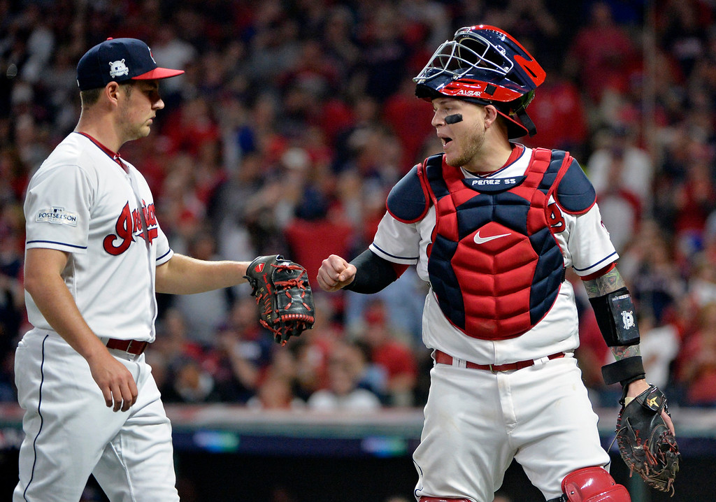 . Cleveland Indians catcher Roberto Perez bumps fists with starting pitcher Trevor Bauer during the fourth inning against the New York Yankees in Game 1 of a baseball American League Division Series, Thursday, Oct. 5, 2017, in Cleveland. (AP Photo/Phil Long)