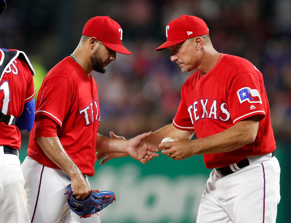 . Texas Rangers starting pitcher Martin Perez, left, hands the ball to manager Jeff Banister during the sixth inning of a baseball game against the Cleveland Indians, Friday, July 20, 2018, in Arlington, Texas. (AP Photo/Jim Cowsert)