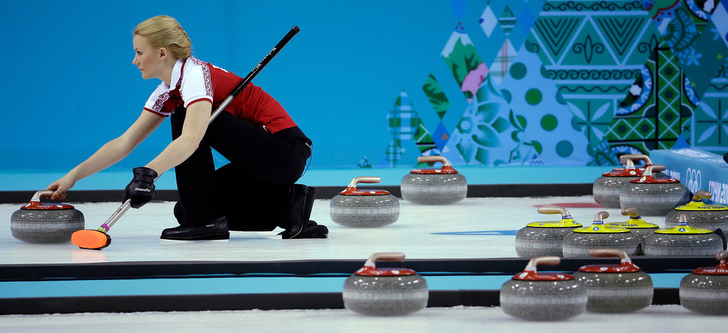 . Russia\'s Alexandra Saitova gets ready to deliver the rock to her sweepers during a round robin match against Britain at the 2014 Winter Olympics, Monday, Feb. 17, 2014, in Sochi, Russia. (AP Photo/Morry Gash)