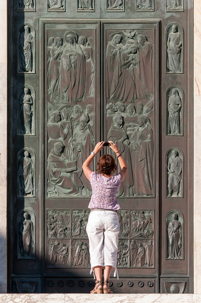 Tourist Takes Pictures of Bronze Portal of Cathedral of Siena (Duomo di Siena), Tuscany, Italy