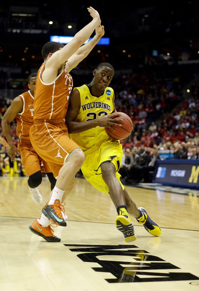 Description of . Michigan guard Caris LeVert (23) drives against Texas guard Javan Felix (3) during the first half of a third-round game of the NCAA college basketball tournament Saturday, March 22, 2014, in Milwaukee. (AP Photo/Morry Gash)
