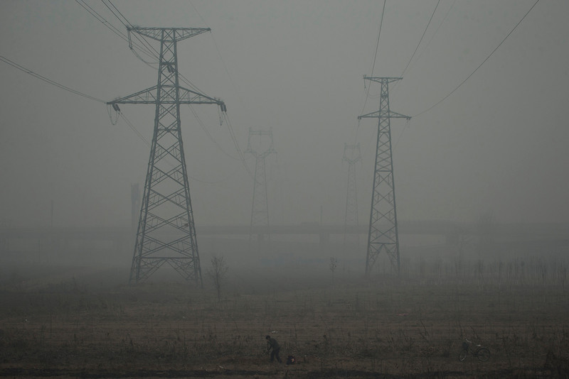 . A farmer shovels in a field near electric pylons in heavy haze on a severely polluted day in Shijiazhuang, in northern China\'s Hebei province, Wednesday, Feb. 26, 2014. (AP Photo/Alexander F. Yuan)