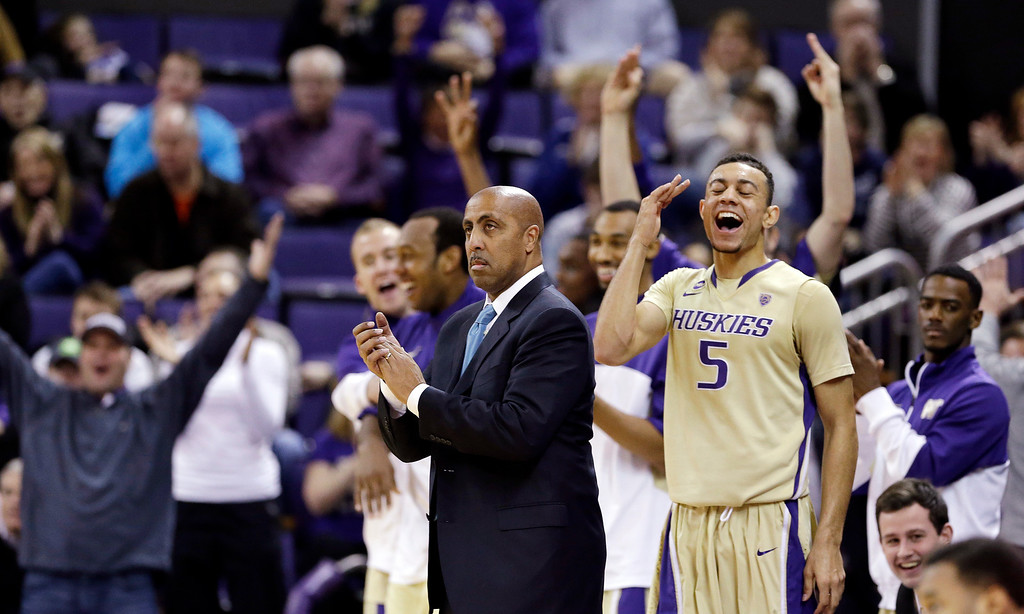 . Washington head coach Lorenzo Romar watches as Nigel Williams-Goss(5) cheers from the bench against Colorado in the second half of an NCAA men\'s basketball game Sunday, Jan. 12, 2014, in Seattle. Washington won 71-54. (AP Photo/Elaine Thompson)