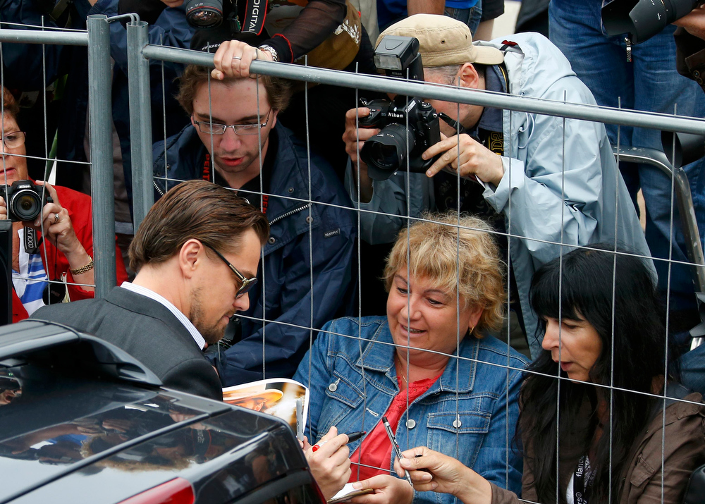 . Cast member Leonardo DiCaprio (L) signs autographs as he arrives at the Festival Palace to attend a photocall for the film \'The Great Gatsby\' before the opening of the 66th Cannes Film Festival in Cannes May 15, 2013. The 66th Cannes Film Festival will run from May 15 to May 26.         REUTERS/Yves Herman