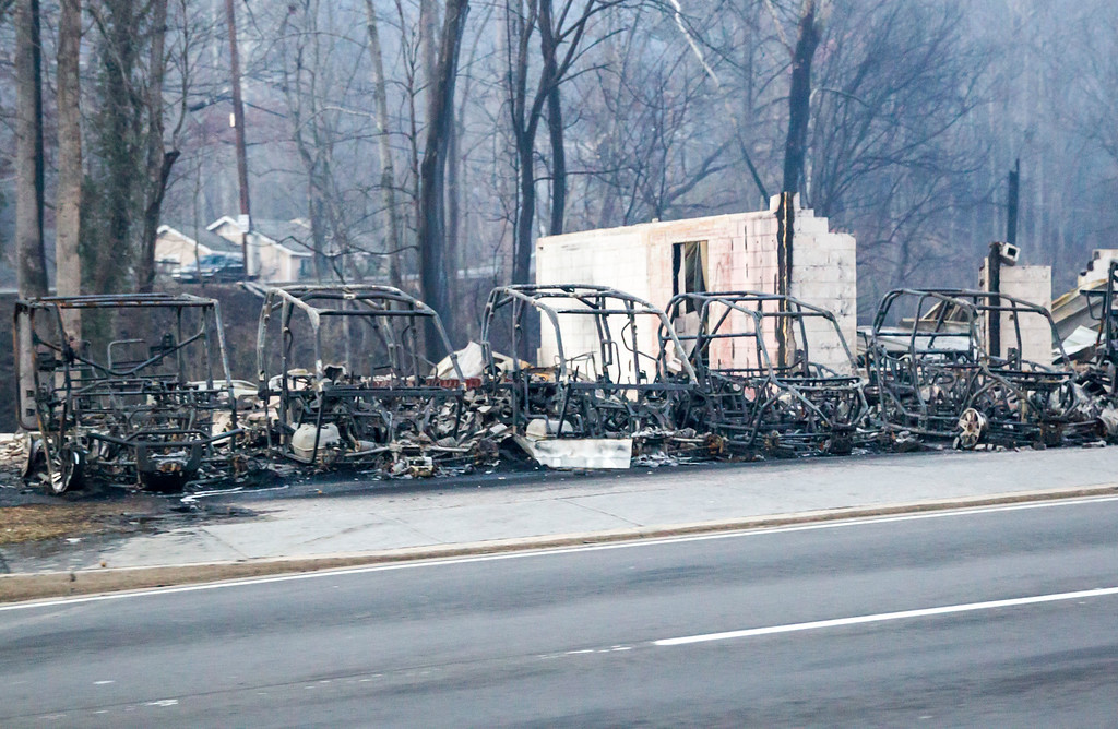 . Burned out frames side-by-side utility vehicles sit at the side of the road in Gatlinburg, Tenn., Tuesday, Nov. 29, 2016. The fatal wildfires swept over the tourist town the night before, causing widespread damage. (AP Photo/Erik Schelzig)