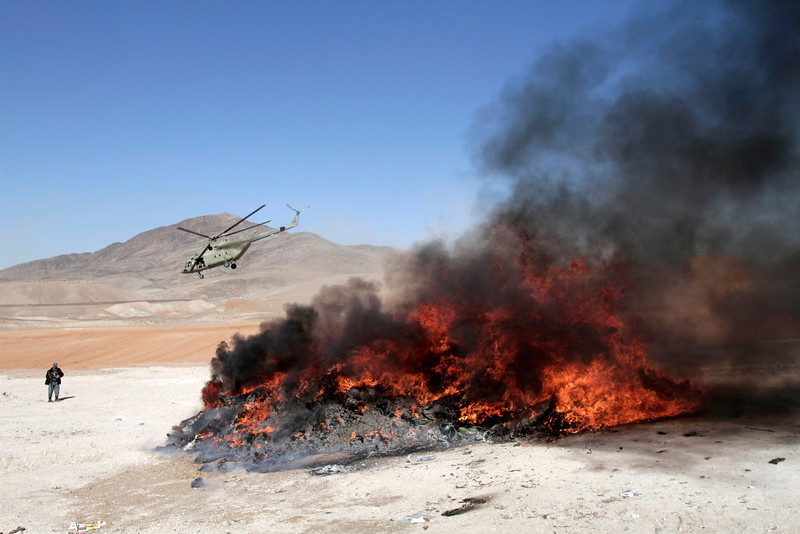 . A helicopter is seen behind of a pile of confiscated drugs and alcohol during a burning ceremony in Jalalabad, east of Kabul, Afghanistan, Wednesday, Dec. 19, 2012. Around 61 tons of opium, heroin, alcohol and hashish were set on fire, officials said. (AP Photo/Rahmat Gul)