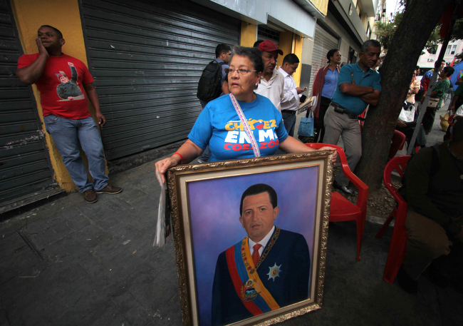 Description of . A woman holds a painting of President Hugo Chavez as supporters gather around Bolivar square after his return to the country in Caracas, Venezuela, Monday, Feb. 18, 2013.  Chavez returned to Venezuela early Monday after more than two months of medical treatment in Cuba following cancer surgery. The government didn't offer an explanation as to why Chavez made his surprise return while he is undergoing other treatments that have not been specified.(AP Photo/Fernando Llano)
