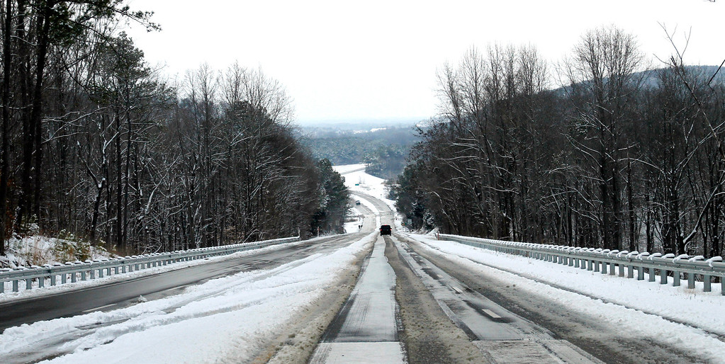 . State highway 31 is closed to traffic due to icy road conditions Tuesday, Feb. 11, 2014, in Vinemont, Ala. Some vehicles bypassed the closure before highway could be plowed. A winter storm dropped several inches of snow on North Alabama overnight and more is expected. (AP Photo/Butch Dill)