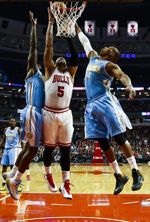 . Chicago Bulls forward Carlos Boozer (C) battles for a rebound with Denver Nuggets players center J.J. Hickson (L) and guard Randy Foye (R) in the first half of their NBA game at the United Center in Chicago, Illinois, USA, 21 February 2014  EPA/TANNEN MAURY