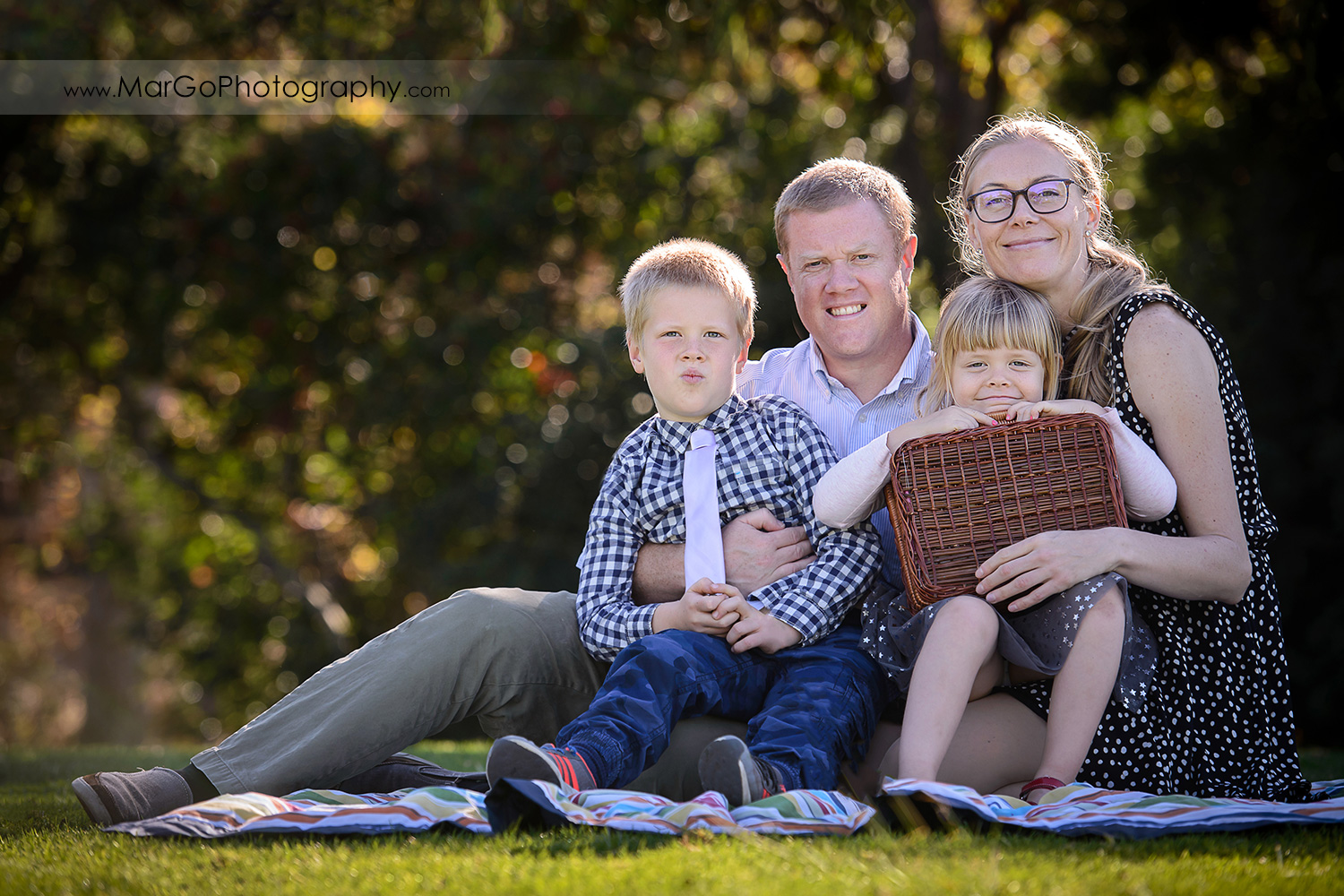 portrait of family of 4 sitting on the grass at Mountain View Shoreline Lake Park