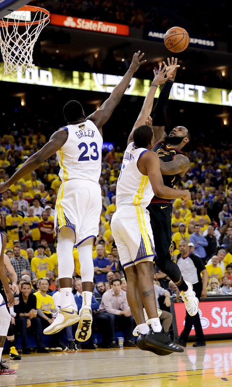 . Cleveland Cavaliers forward LeBron James, right, shoots against Golden State Warriors forward Draymond Green and forward Kevon Looney during the second half of Game 1 of basketball\'s NBA Finals in Oakland, Calif., Thursday, May 31, 2018. (AP Photo/Marcio Jose Sanchez)