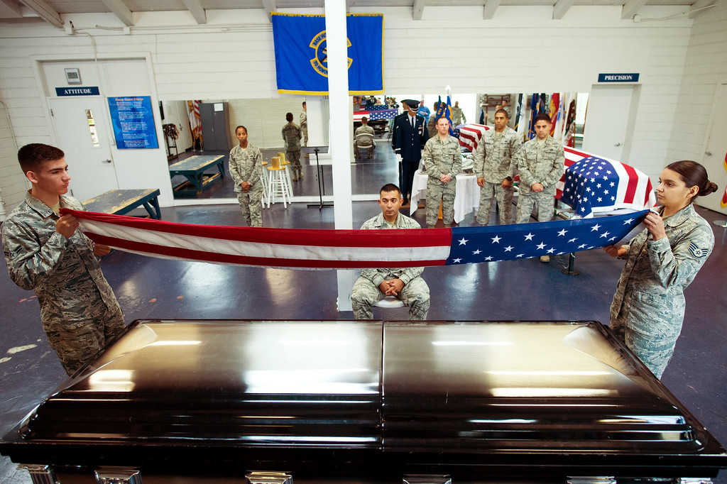 . Airman Gilbert Garcia, left, and Staff Sgt. Anahi Ledezma practice folding the U.S. flag over a casket at March Air Reserve Base in Riverside, Calif. on Wednesday, May 13, 2015. (Photo by Watchara Phomicinda/ Los Angeles Daily News)