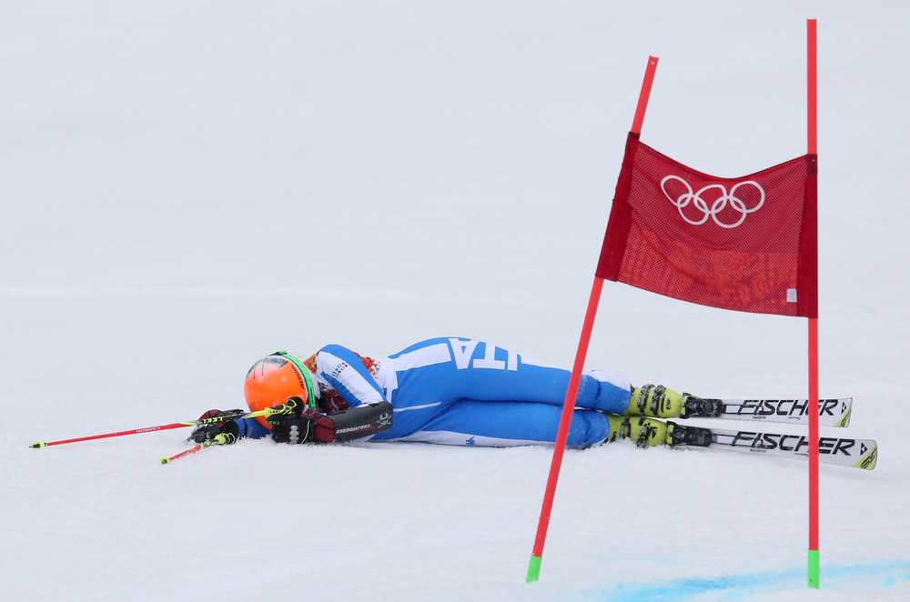 Description of . Italy's Denise Karbon lies on the course after crashing in the second run of the women's giant slalom at the Sochi 2014 Winter Olympics, Tuesday, Feb. 18, 2014, in Krasnaya Polyana, Russia.(AP Photo/Alessandro Trovati)