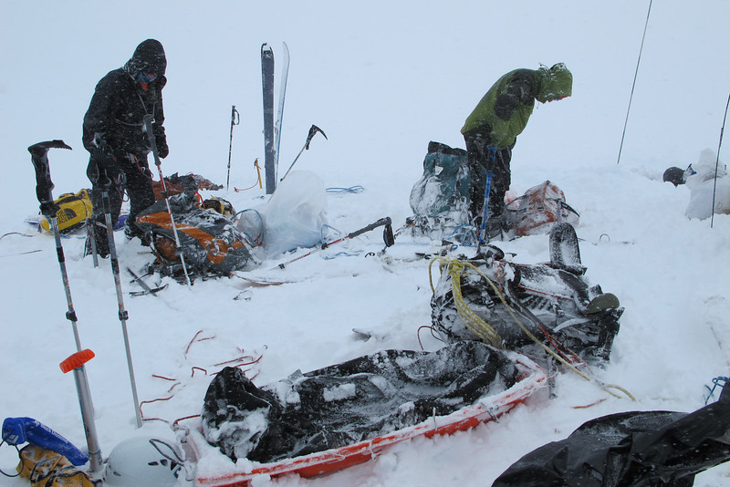 """In 5 hrs, by 6am, through Kahiltna Glacier we have been in Camp 1 (C1) at 7,800 ft (2.377m). The rain started!!! June 26th at 5am (Day # 4) we continued with ~80 pounds (36kg) in backpack and sled to the """"cash-in"""" spot at about 9,780ft (2.981m). We were there in ~ 4.5 hrs, dug a hole ~3ft (1m) deep and left our gear/load. ...After rain, snow started..."""