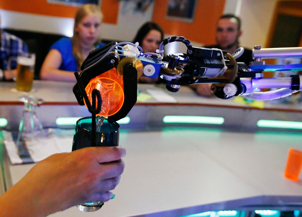 ". Humanoid robot bartender ""Carl\"" pours a spirit into the cocktail shaker of a bartender to prepare a drink for a guest at the Robots Bar and Lounge in the eastern German town of Ilmenau, July 26, 2013. \""Carl\"", developed and built by mechatronics engineer Ben Schaefer who runs a company for humanoid robots, prepares spirits for the mixing of cocktails and is able to interact with customers in small conversations. Picture taken July 26, 2013. REUTERS/Fabrizio Bensch"