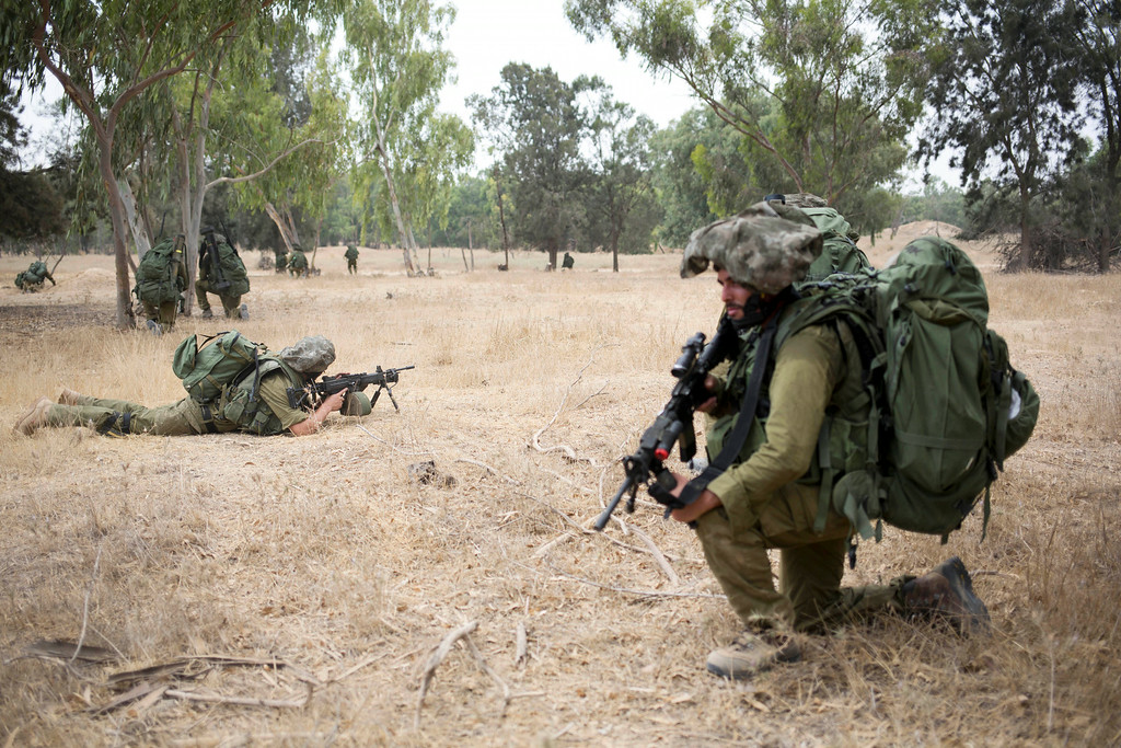 . Israeli soldiers take positions during a drill near the Israel and Gaza border, Tuesday, July 22, 2014. Israeli airstrikes pummeled a wide range of targets in the Gaza Strip on Tuesday as the U.N. chief and the U.S. secretary of state began an intensive effort to end more than two weeks of fighting that has killed hundreds of Palestinians and dozens of Israelis. (AP Photo/Dusan Vranic)