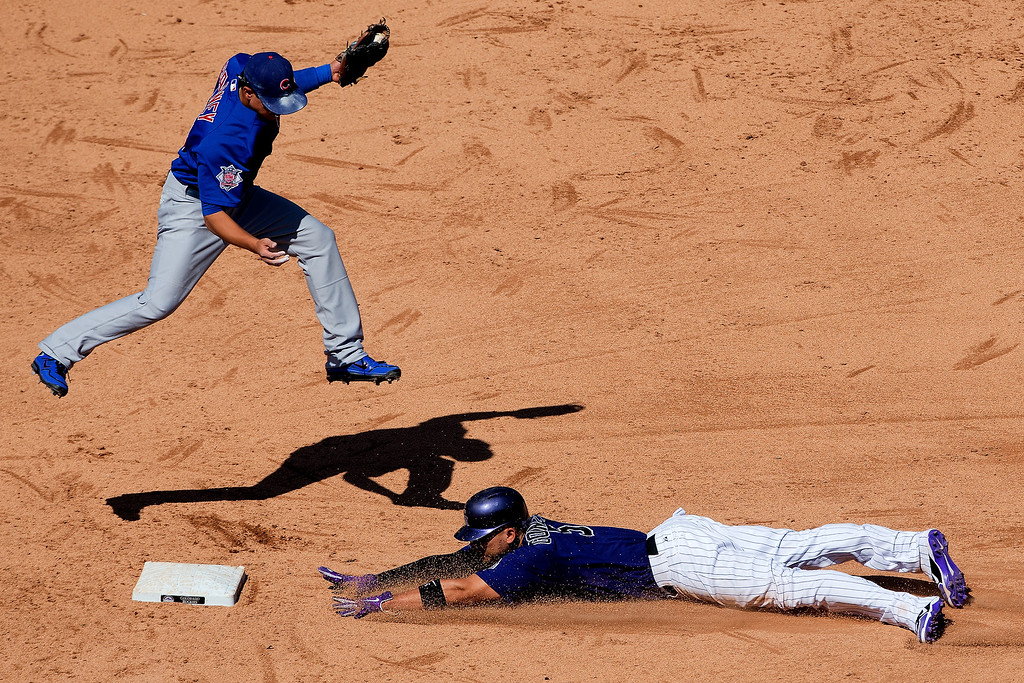 . Carlos Gonzalez #5 of the Colorado Rockies slides in safely for his second stolen base of the game as second baseman Darwin Barney #15 of the Chicago Cubs has to jump to make the catch during the sixth inning at Coors Field on July 21, 2013 in Denver, Colorado. The Rockies defeated the Cubs 4-3.  (Photo by Justin Edmonds/Getty Images)