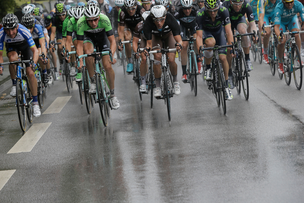 . The pack rides in the rain during the eighth stage of the Tour de France cycling race over 161 kilometers (100 miles) with start in Tomblaine and finish in Gerardmer, France, Saturday, July 12, 2014. (AP Photo/Laurent Cipriani)