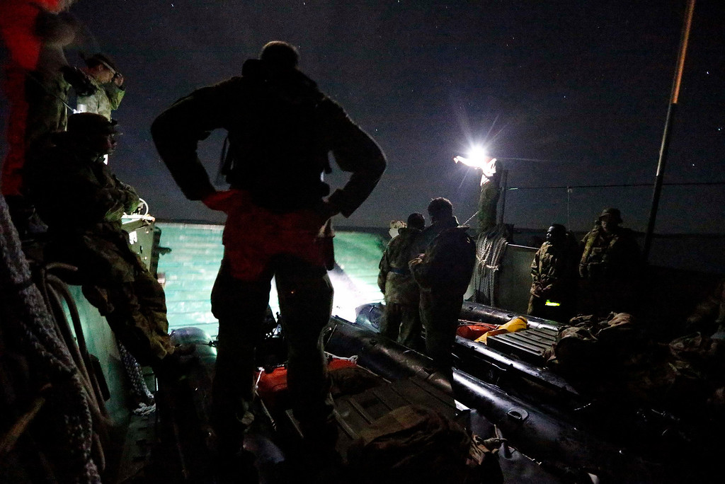 . Patrol Commander, Andrew \'Dusty\' Miller (L) of Australia\'s North West Mobile Force (NORFORCE) unit watches as his soldiers prepare inflatable boats aboard a transport vessel after leaving Gove, also known as Nhulunbuy, 650 km (404 miles) east of Darwin, in the Northern Territory, Australia July 16, 2013. NORFORCE is a surveillance unit that employs ancient Aboriginal skills to help in the seemingly impossible task of patrolling the country\'s vast northwest coast. NORFORCE\'s area of operations is about 1.8 million square km (700,000 square miles), covering the Northern Territory and the north of Western Australia. Aboriginal reservists make up a large proportion of the 600-strong unit, and bring to bear their knowledge of the land and the food it can provide. Fish, shellfish, turtle eggs and even insects supplement rations during the patrol, which is on the lookout for illegal foreign fishing vessels and drug smugglers, as well as people smugglers from neighboring Indonesia. Picture taken July 16, 2013. REUTERS/David Gray