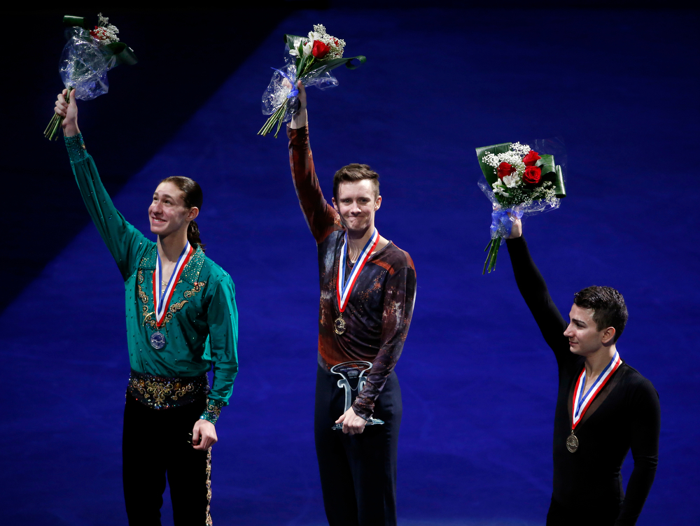 . The top three men\'s skaters, from left, Jason Brown (second place), Jeremy Abbott (first place) and Max Aaron (third place) wave their flowers on the awards stand at the U.S. Figure Skating Championships in Boston, Sunday, Jan. 12, 2014. (AP Photo/Elise Amendola)
