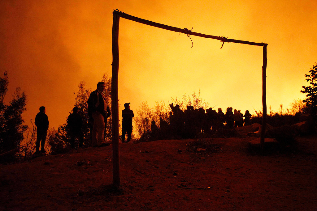 . People watch as a forest fire destroys homes in Valparaiso, Chile, Sunday April 13, 2014. Authorities say the fires have destroyed hundreds of homes, forced the evacuation of thousands and claimed the lives of at least seven people.  ( AP Photo/ Luis Hidalgo)