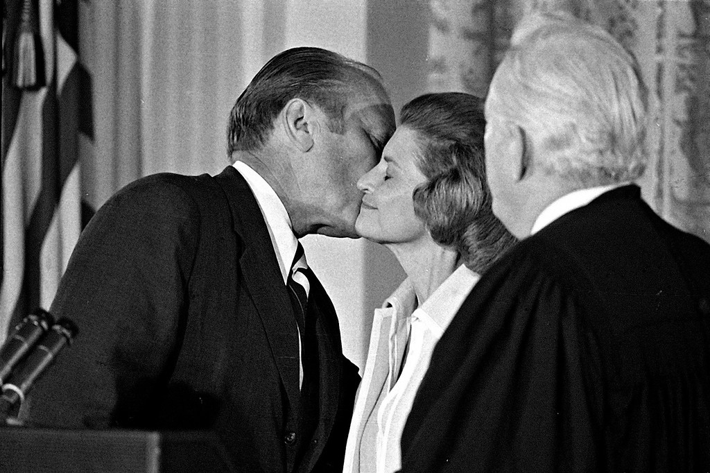 . President Gerald R. Ford kisses his wife Betty, Aug. 9, 1974, after he was sworn in as 38th President of the United States by Chief Justice Warren Burger, right, in the East Room of the White House.  (AP Photo)