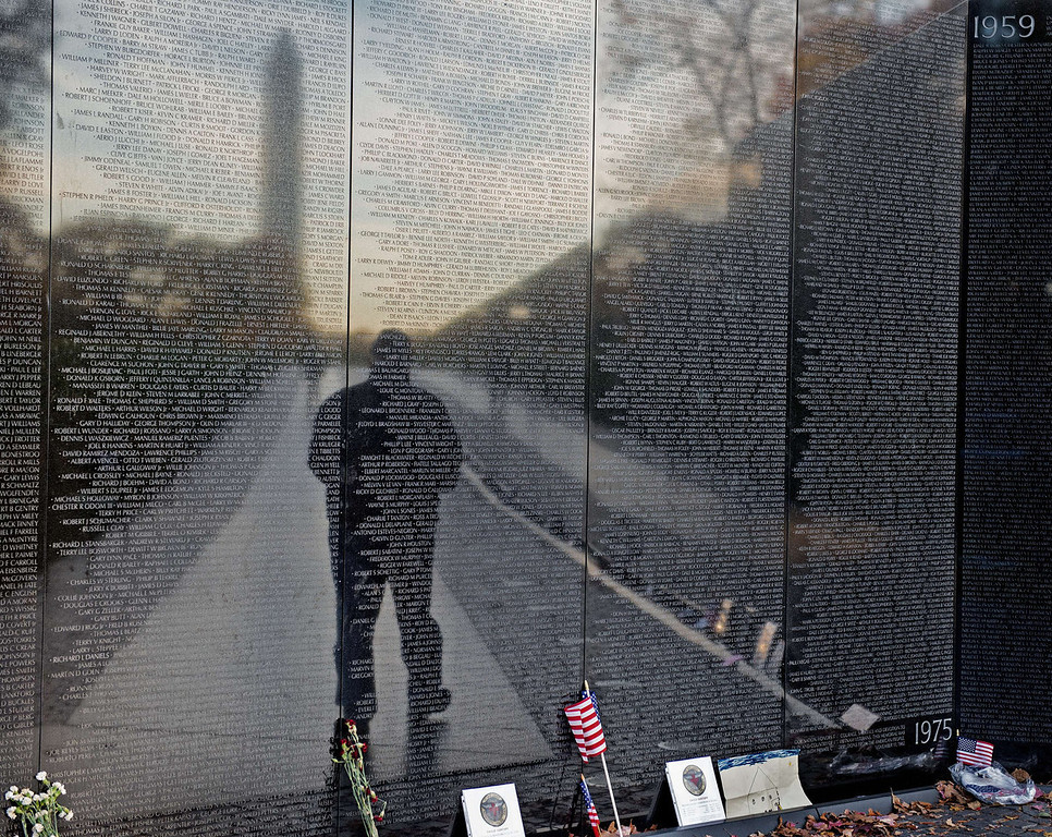 . An unidentified man is seen in the reflection of the Viet Nam Memorial wall on Veteran\'s Day November 11, 2013  as he pays his respects to fallen veterans in Washington, DC.    PAUL J. RICHARDS/AFP/Getty Images