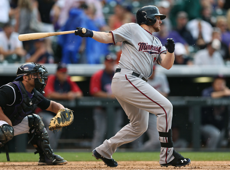 . Minnesota Twins pinch-hitter Chris Parmelee, right, follows the flight of his single to drive in two runs as Colorado Rockies catcher Michael McKenry looks on in the eighth inning of the Twins\' 9-3 victory in an interleague baseball game in Denver on Saturday, July 12, 2014. (AP Photo/David Zalubowski)
