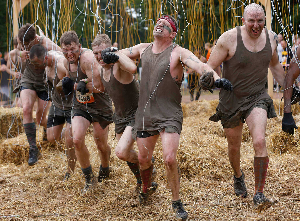 """. Participants of the \""""Tough Mudder\"""" endurance event series run through the \""""Electroshock Therapy\"""" obstacle made of electrical wires holding some 10,000 Volts in the Fursten Forest, a former British Army training ground near the north-western German city of Osnabrueck July 13, 2013. The hardcore but un-timed event over 16 km (10 miles) was designed by British Special Forces to test mental as well as physical strength. Some 4,000 competitors had to overcome obstacles of common human fears, such as fire, water, electricity and heights.   REUTERS/Wolfgang Rattay"""