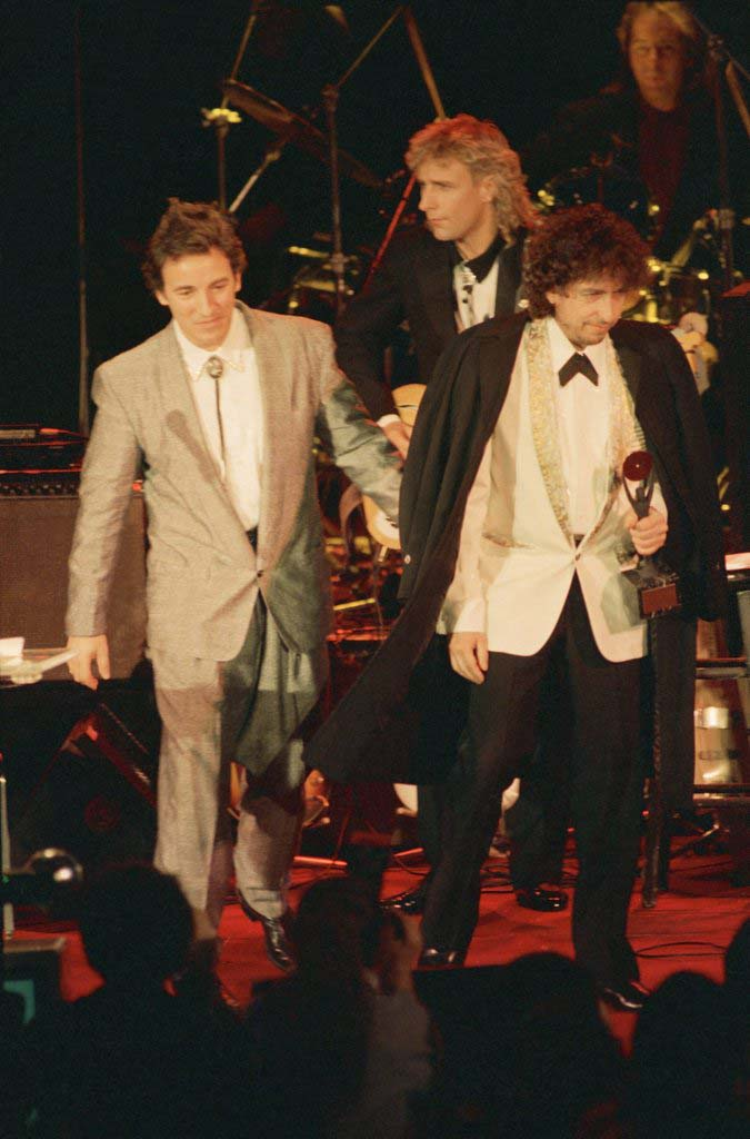 . Rock superstars Bruce Springsteen, left, and Bob Dylan, right, appears at Rock \'n Roll Hall of Fame induction ceremonies at New York\'s Waldorf-Astoria Hotel, Wednesday, Jan. 21, 1988. Dylan was one of five rock legends inducted into the hall during the ceremonies, while Springsteen must wait his turn; artists do not become eligible until 25 years after releasing their first recording. (AP Photo/Ron Frehm)