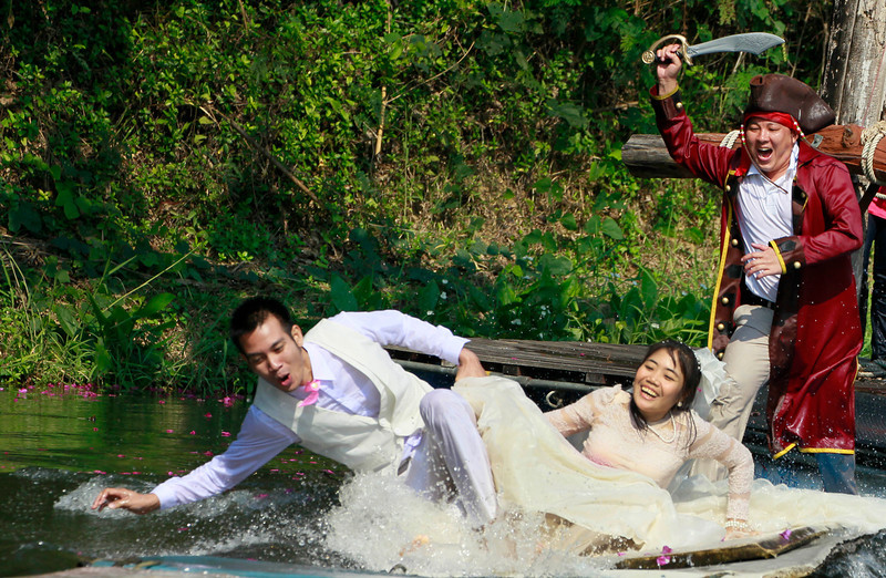 . Sornwich Changtor, left, and Rungnapa Changtor are chased by an actor in pirate costume during a part of an adventure-themed wedding ceremony in Prachinburi province, Thailand, Wednesday, Feb. 13, 2013, on the eve of Valentine\'s Day. Three couples participated in the ceremony. (AP Photo/Wason Wanichakorn)
