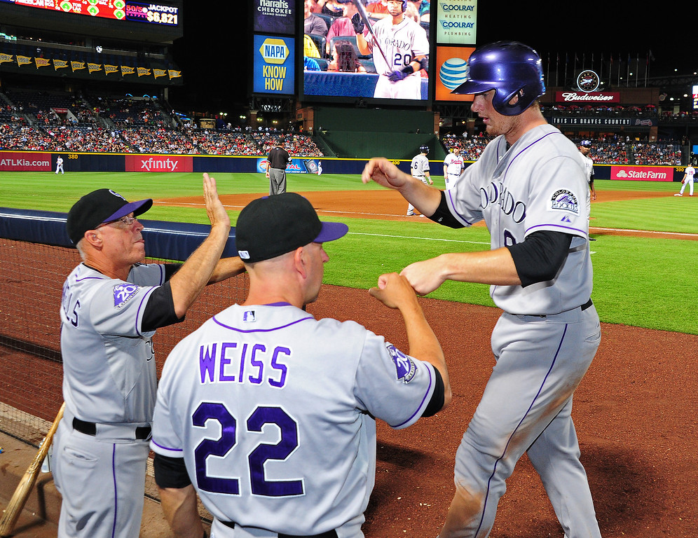 . D. J. LeMahieu #9 of the Colorado Rockies is congratulated by teammates after scoring a 7th inning run against the Atlanta Braves at Turner Field on August 1, 2013 in Atlanta, Georgia. (Photo by Scott Cunningham/Getty Images)