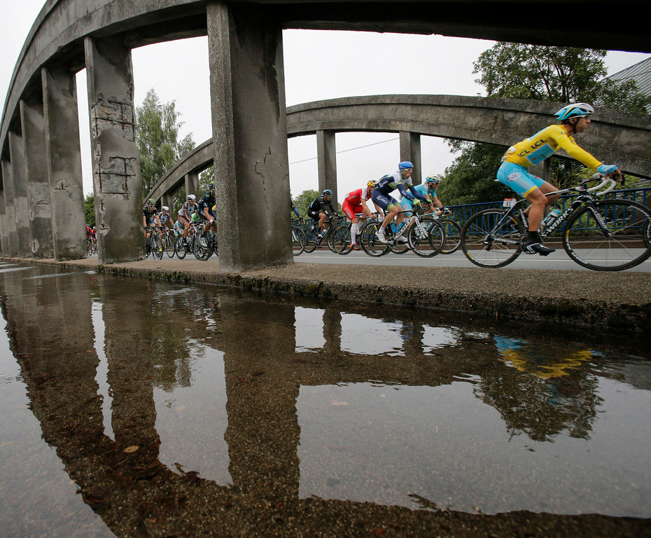 . The pack with Italy\'s Vincenzo Nibali, wearing the overall leader\'s yellow jersey, passes over a bridge with a flooded sidewalk during the sixth stage of the Tour de France cycling race over 194 kilometers (120.5 miles) with start in Arras and finish in Reims, France, Thursday, July 10, 2014. (AP Photo/Christophe Ena)