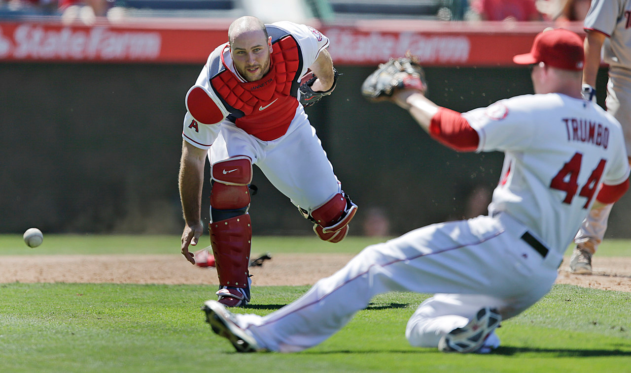 . Angels catcher Chris Iannetta, left, watches first baseman Mark Trumbo slide to try to catch a foul ball bunt attempt by Minnesota\'s Doug Bernier during the ninth inning. (AP Photo/Jae C. Hong)