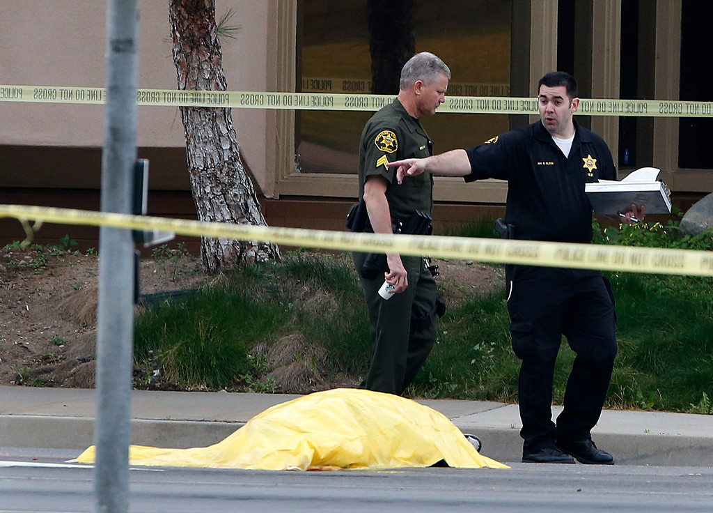 . Investigators walk past a tarp covered body in Orange, Calif., Tuesday, Feb. 19, 2013. Police say a chaotic 25-minute shooting spree through Orange County left a trail of dead and injured victims before the shooter killed himself. Orange County sheriff\'s spokesman Jim Amormino say there are at least six crime scenes with three people, including the suspected gunman, dead and several others wounded. Tustin police Supervisor Dave Kanoti said the shootings started with an apparent carjacking just after 5 a.m. Tuesday in an unincorporated Ladera Ranch area of Orange County. (AP Photo/Jae C. Hong)