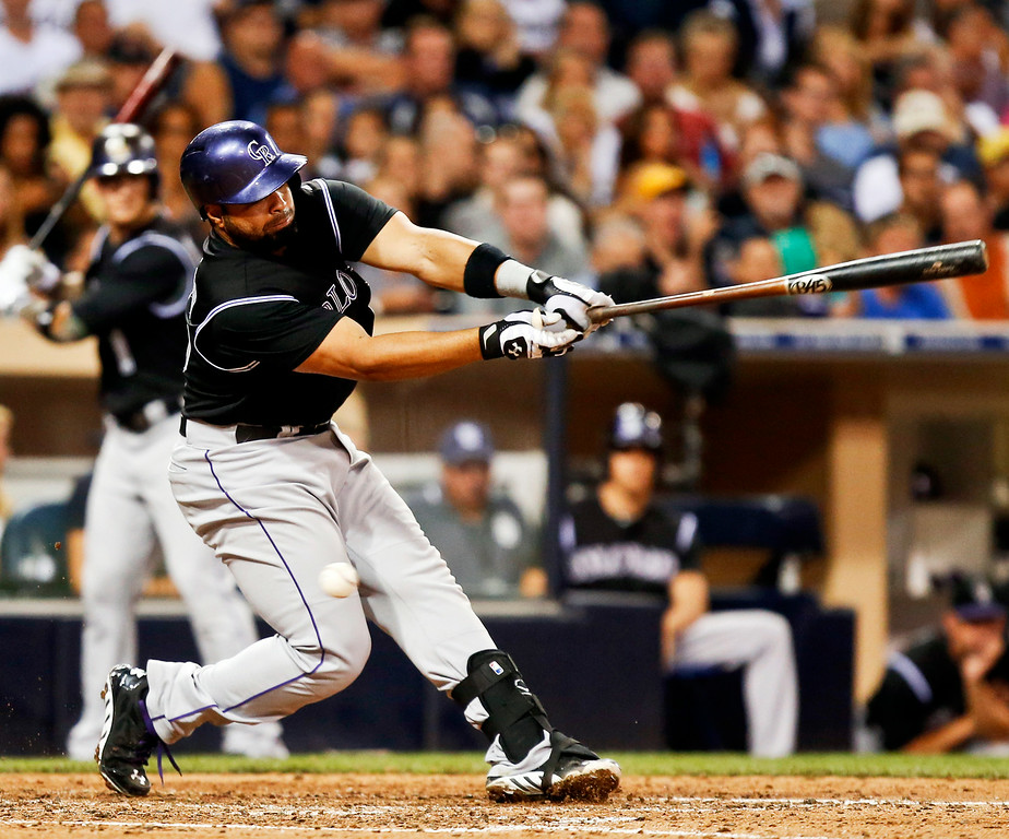 . Colorado Rockies\' Wilin Rosario swings over the top of an off-speed pitch to strike out with two runners in scoring position to end the sixth inning of a baseball game against the San Diego Padres, Tuesday, Aug. 12, 2014, in San Diego. (AP Photo/Lenny Ignelzi)